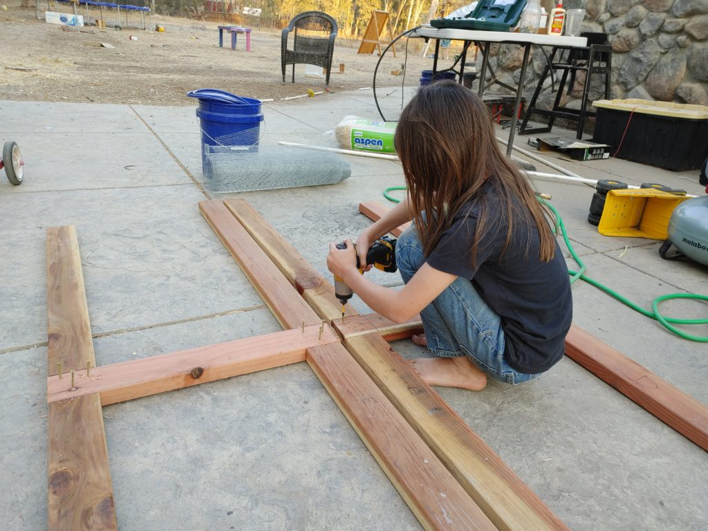 Pre-teen child using a cordless impact driver to put screws into a wooden frame